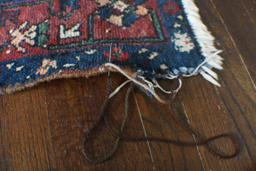 Sewing the border of a fraying oriental rug