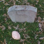 Doll face in front of a landscaping block tombstone for Halloween